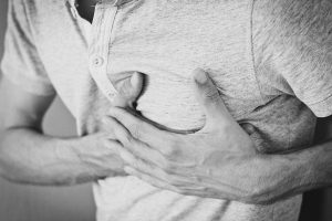Man holding chest due to pain