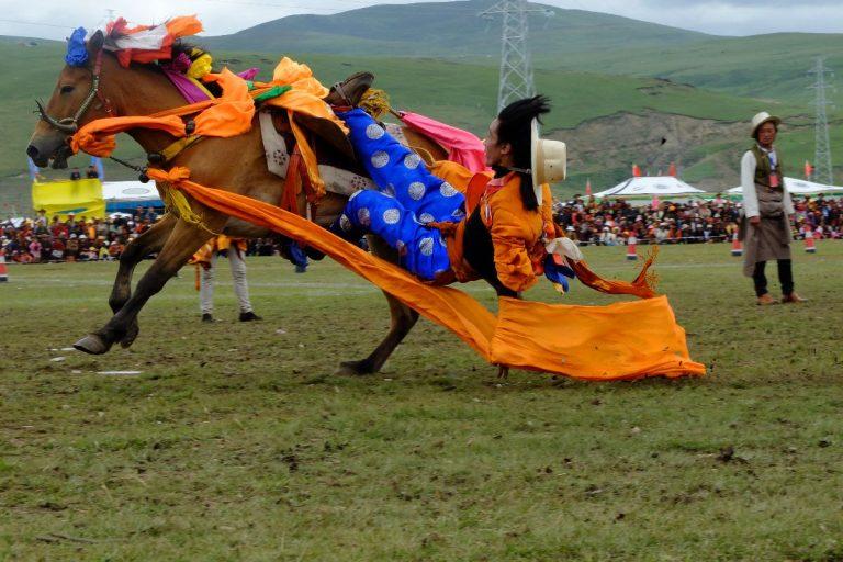 Tibtan Man riding horse at Nagchu Horse Racing Festival in Tibet