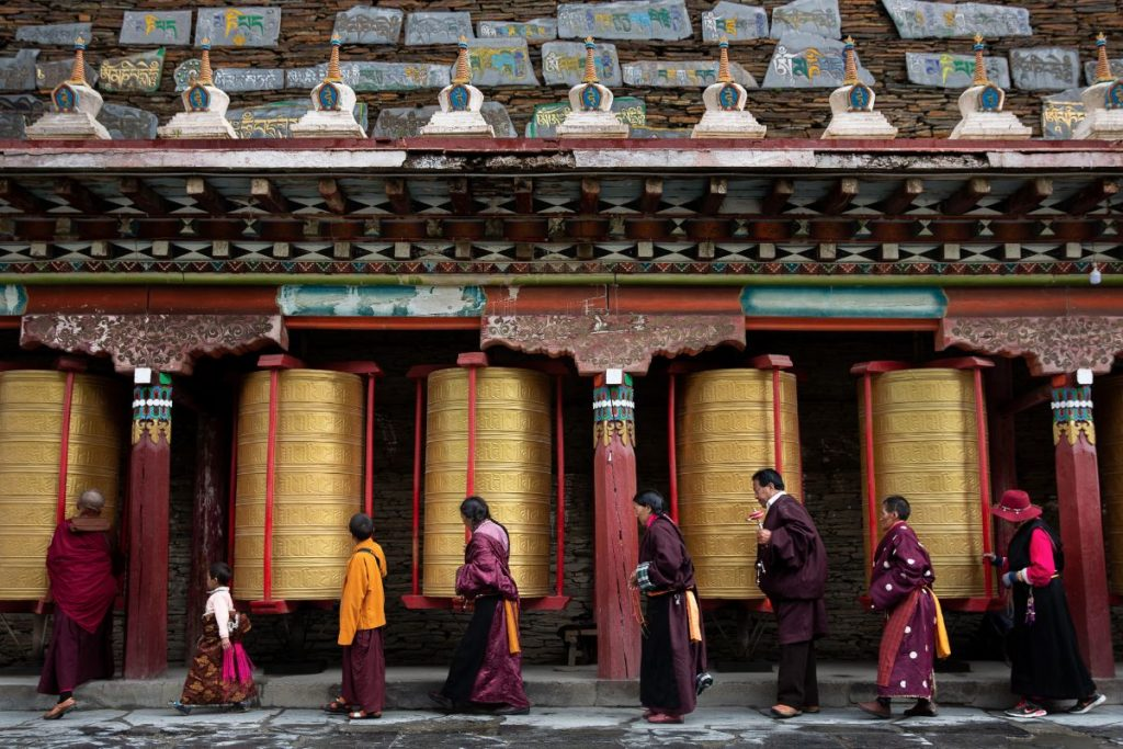 Tibetans waking and touching the fortune prayer wheels