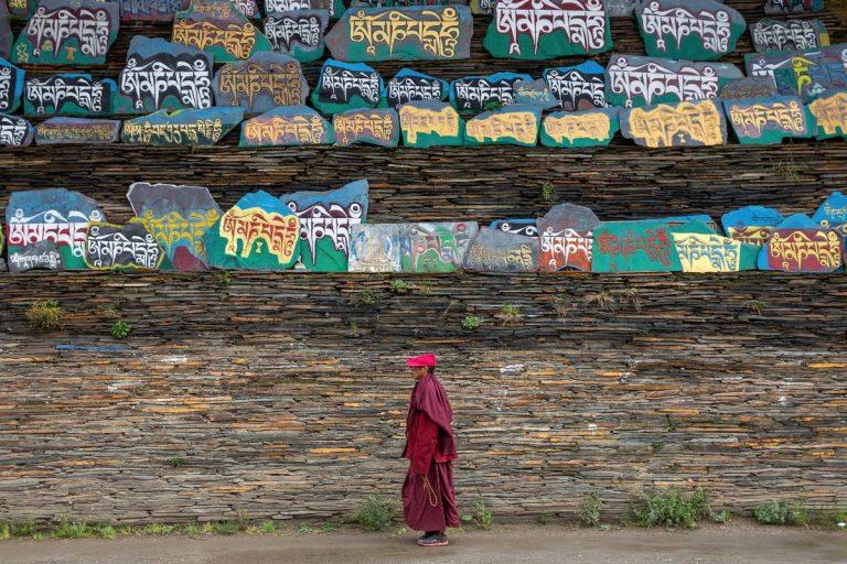 Tibetan monks standing below Buddhist scripts
